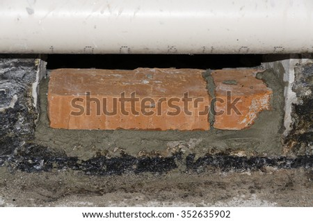 positioning a brick with cement at a construction site