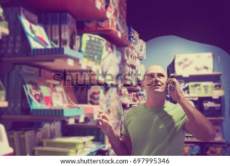 Positive adult man in toy store calls by telephone to the wife to consult