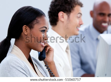 Positive Afro-American businesswoman talking on phone in the office