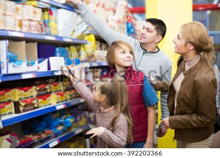 positive american parents with two kids choosing crispy flakes in shop