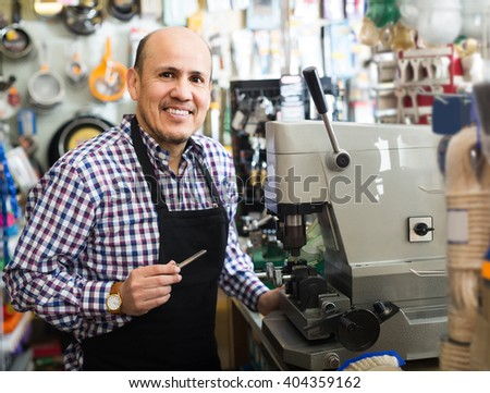 positive american senior professional with different types of keys in locksmith - stock photo