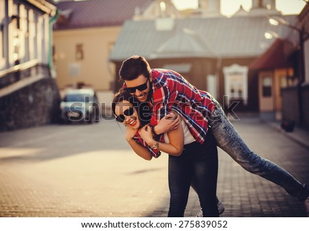 positive and carefree couple having fun in city - stock photo