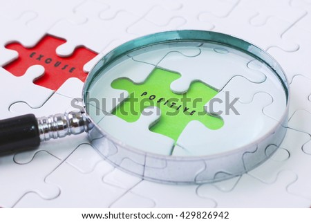 POSITIVE and EXCUSE  puzzle with magnifier glass - stock photo