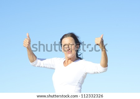 Positive and happy active retired mature woman posing with thumbs up and smile, isolated with blue sky as background and copy space. - stock photo