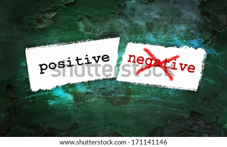 Positive and negative written on piece of paper - stock photo