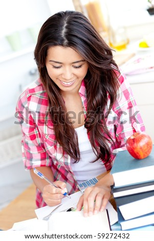 Positive asian student doing her homework at home in the kitchen - stock photo