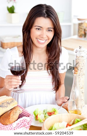 Positive asian woman holding a glass of wine having dinner in the kitchen - stock photo