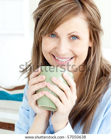 Positive attractive businesswoman holding a cup smiling at the camera