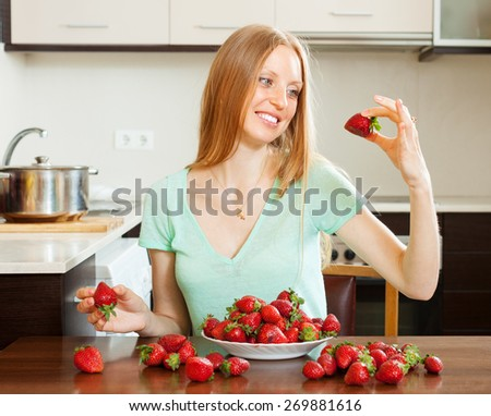 Positive blonde long-haired woman eating strawberry in home kitchen  - stock photo