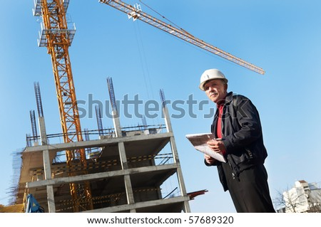 positive builder inspector worker at construction site - stock photo