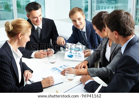 Positive business people holding a meeting to sum up the results of the year - stock photo