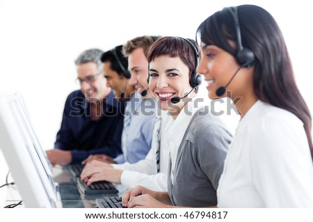 Positive business people using headset in a call center - stock photo