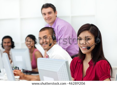 Positive business people with headset on working in the office - stock photo