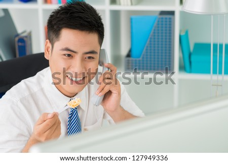 Positive business worker answering lunchtime call