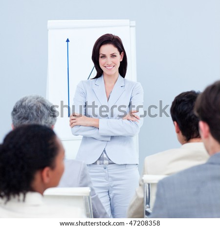 Positive businesswoman doing a presentation to her colleagues - stock photo