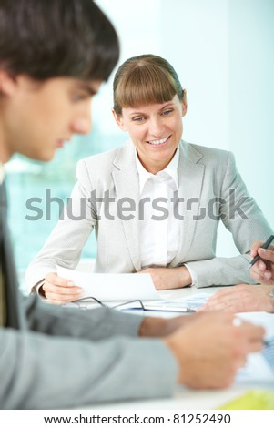 Positive businesswoman sitting at table with her colleagues