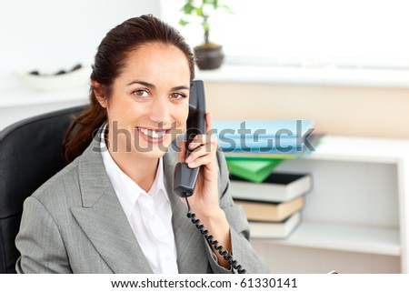 Positive businesswoman talking on phone sitting in her office at her desk - stock photo