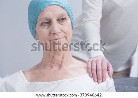 Positive cancer woman and person holding hand on her arm - stock photo