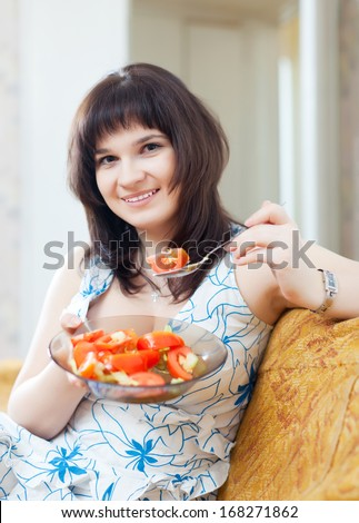 positive casual woman eats veggie salad on sofa at home interior