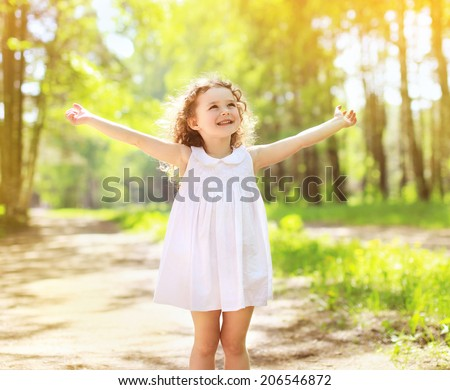 Positive charming curly little girl enjoying summer sunny day, expression emotions, having fun, happy child walking in summer day - stock photo
