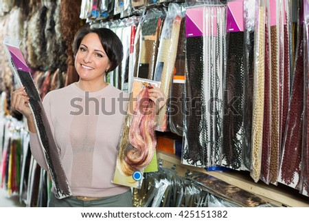 Positive cheerful smiling middle aged woman purchasing hair extension in salon - stock photo