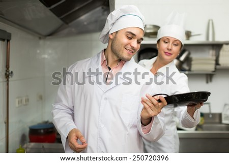 Positive chef with assistant cooking at professional kitchen in the restaurant. Focus on man