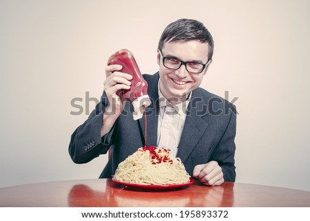 Positive consumerism concept. Happy businessman pouring ketchup on large dish of pasta.