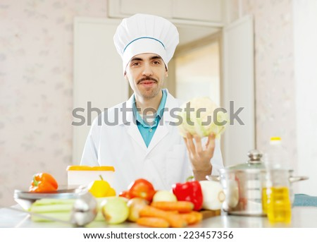 Positive cook man cooking with cauliflower at kitchen - stock photo