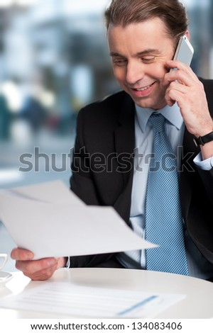 Positive corporate guy communicating on phone with reports in hand. - stock photo