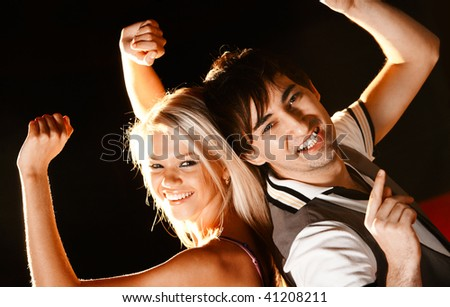 Positive couple looking at camera with smiles during disco