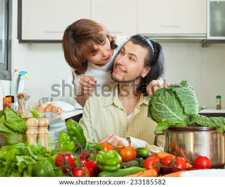 Positive couple preparing vegetable salad in my house