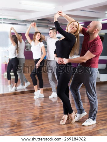 Positive couples enjoying of partner dance and smiling indoor - stock photo