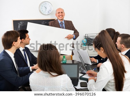 Positive creative colleagues discussing new development plan at poster - stock photo