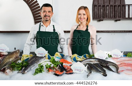 Positive cute shop assistants selling fresh fish and chilled seafood