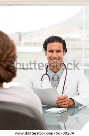 Positive doctor during a appointment with a female patient in his office - stock photo