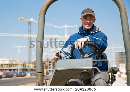 Positive driver worker during road works with construction equipment - stock photo