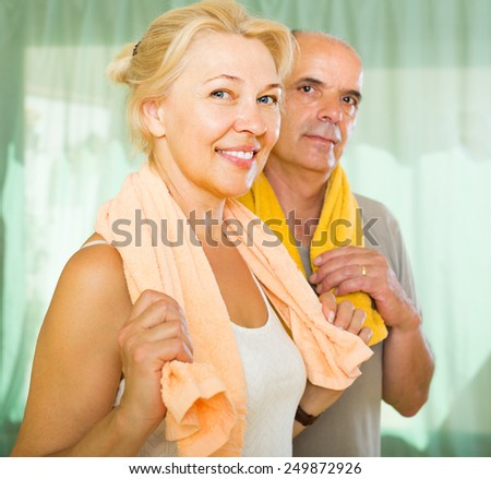 Positive elderly couple smiling after training indoor. Focus on woman