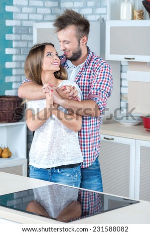 Positive emotions on the kitchen. Beautiful pair is standing on the kitchen and hugging. They are discussing the ideal recipe for tasty and healthy meal - stock photo