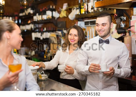 Positive european female drinking wine at counter and chatting with bartenders
