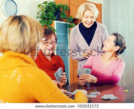 Positive european senior female friends staking money during bridge