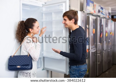 Positive family couple buying domestic refrigerator in supermarket - stock photo
