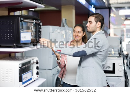 Positive family couple choosing new microwave in supermarket. Focus on the man - stock photo