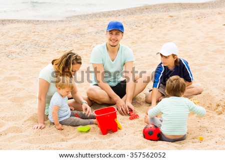 Positive family of five sitting at sandy beach and resting - stock photo