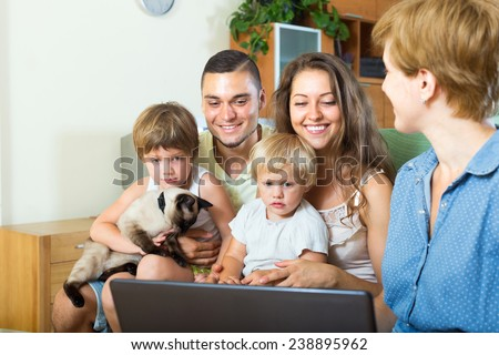 Positive family of four sitting on the couch and listening to the insurance agent - stock photo
