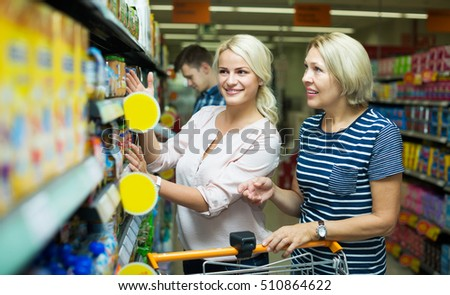 Positive female clients buying infant food in jars at supermarket