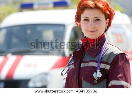 Positive female doctor paramedic on ambulance vehicle background - stock photo