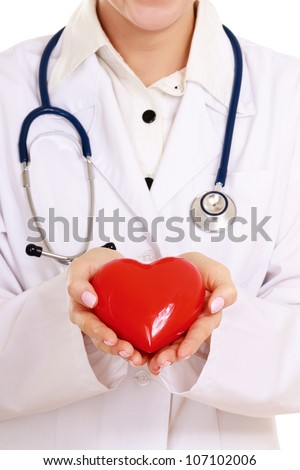 Positive female doctor standing with stethoscope and red heart symbol isolated on white background - stock photo