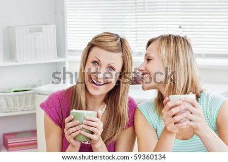 Positive female friends holding a cup of coffee at home in the living-room