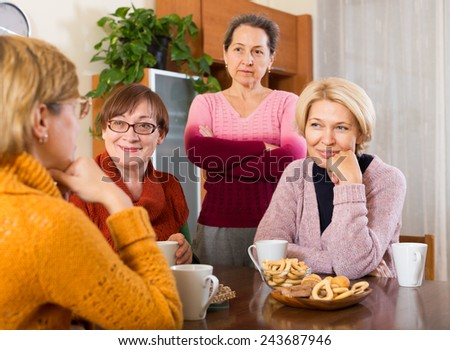 Positive female pensioners drinking tea at the table in living room - stock photo