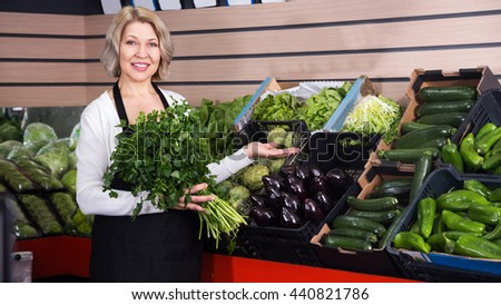 Positive female seller offering good price for herbs in grocery